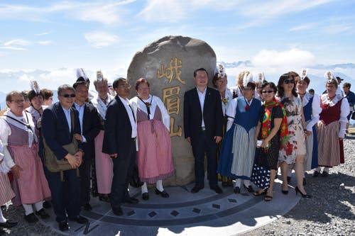 Der Stein steht: Die chinesische Delegation freut sich sichtlich zwischen der Trachtengruppe Arth Goldau. (Bild: pd)