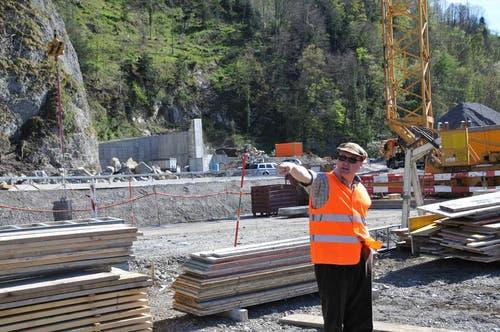Gesamtprojektleiter Sepp Berwert aus Sarnen informiert auf der Baustelle der neuen Kantonsstrassenbrücke. Im Hintergrund der künftige Geschiebesammler Gorgen mit der bis zu 12 Meter hohen Mauer. (Bild: Robert Hess / Neue OZ)