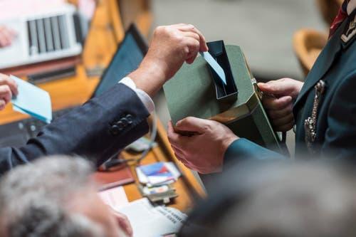 Ein Ratsmitglied wirft den Stimmzettel in die Urne. (Bild: MARCEL BIERI)