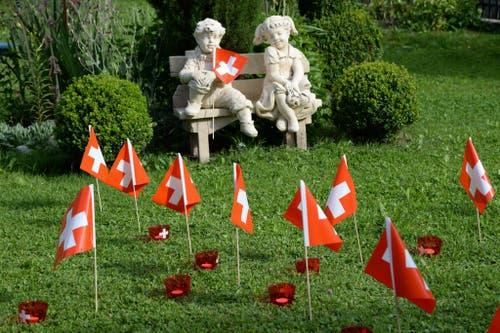 Ein heiteres Pärchen feiert im Garten eines Hauses in Lungern ganz leise Bundesfeiertag. (Bild: Robert Hess / Neue OZ)