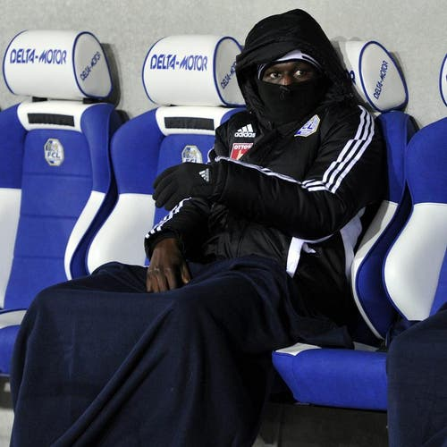Sally Sarr vom FC Luzern sitzt dick verpackt auf der Ersatzbank. (Bild: Keystone)