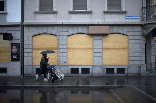 Zürich: Eine Frau mit Kinderwagen und Schirm geht an der Zeughausstrasse an einem mit Holzbrettern verbarrikadierten Geschäft vorbei. (Bild: Keystone)