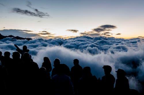 Touristen beobachten den Sonnenaufgang über dem Nebelmeer am Eggishorn. (Bild: Keystone / Dominic Steinmann)