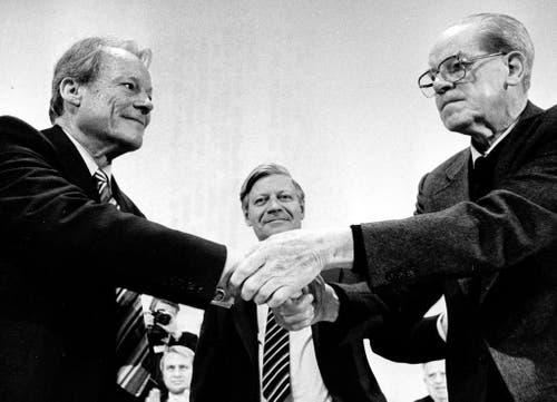 Nach seiner Rede auf dem SPD-Parteitag in Berlin wird der Vorsitzende der Sozialdemokratischen Partei, Willy Brandt (links), beglückwünscht von Bundeskanzler Helmut Schmidt (Mitte) und dem SPD-Fraktionsvorsitzenden Herbert Wehner. (Bild: Keystone)