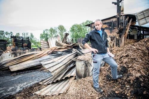 Betriebsleiter Christian Amhof vor der abgebrannten Lagerhalle der Firma Lang Holz Sägewerk AG. (Bild: Roger Grütter / Neue LZ)