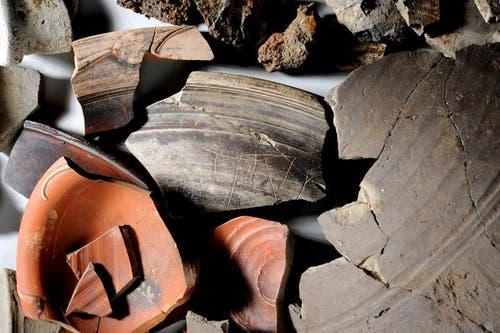 Verschiedene Keramik- und Eisenfunde aus dem Grab mit der Titus-Inschrift. In der Bildmitte das Fragment mit der Titus-Inschrift. (Bild: Kantonsarchäologie Luzern)