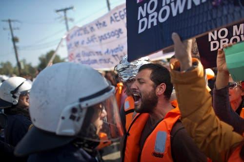Aktivisten verkünden vor dem Registrationscamp Moria ihre Parolen. (Bild: AP/Marko Drobnjakovic)