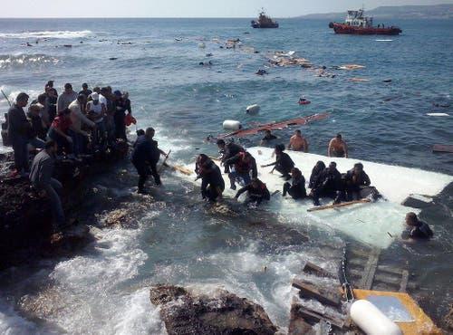 20. April: Eines von vielen Dramen, die sich im Mittelmeer abspielen – Flüchtlinge retten sich nach der Überfahrtt von der Türkei nach Europa auf der griechischen Insel Rhodos an Land, nachdem ihr Schiff auf Grund gelaufen und zerschellt ist. Ein Mann, eine Frau und ein Kind können nur tot geborgen werden. (Bild: EPA / Loukas Mastis)