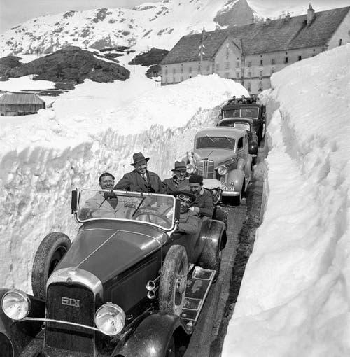 Eine Autokolonne zwischen den Schneemauern vor dem Hospiz auf dem Simplon bei der Wiedereröffnung der Simplonpassstrasse, aufgenommen an Pfingsten im Jahr 1937. (Bild: Keystone)