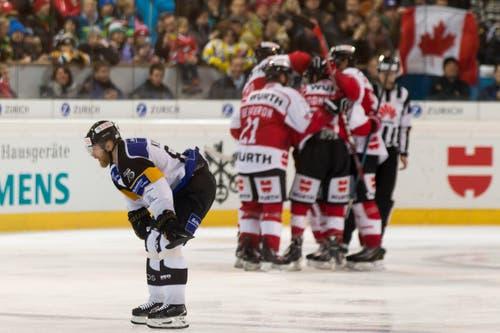 Luganos Linus Klasen ist enttäuscht und das Team Canada feiert das 3 zu 1-Goal im Final des Spengler Cup. (Bild: Keystone/ Pascal Muller)