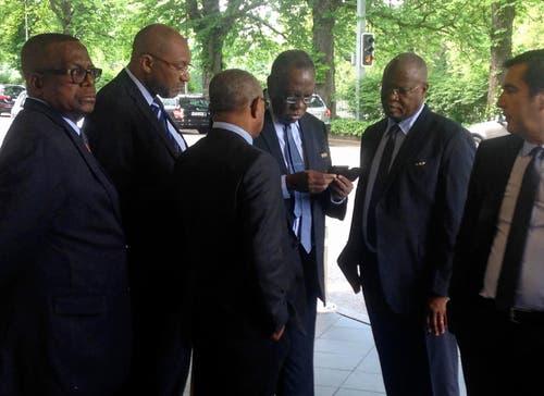 Währenddessen am Mittwoch in Zürich: FIFA-Vizepräsident Issa Hayatou aus Kamerun (dritter von rechts) schaut auf sein Telefon ausserhalb des Hotels. (Bild: AP Photo / Graham Dunbar)