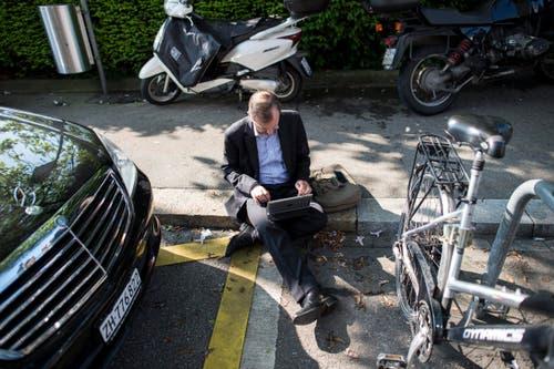 Ein Journalist arbeitet vor dem Fünfstern-Hotel Baur au Lac in Zürich. (Bild: EPA)
