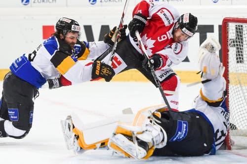 Team Canadas Derek Roy (mitte) gegen Luganos Ryan Glenn und Goalie Elvis Merzlikins. (Bild: EPA/GIAN EHRENZELLER)