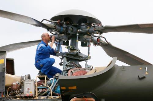 Ein arbeiter säubert den Rotor des Schweizer Super Puma Helikopters SA-332. (Bild: Jacques Brinon)