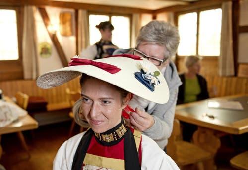 Silvia Käslin zieht Silvia Gut den Kopfschmuck an Im Hintergrund Kobi Würsch. (Bild: Corinne Glanzmann / Neue NZ)