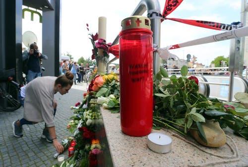 Eine Frau legt beim Eingang des Einkaufszentrum in München Blumen nieder. (Bild: Keystone / Karl-Josef Hildenbrand)