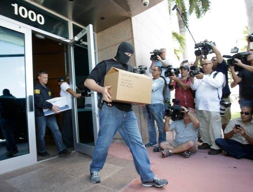 In Miami Beach tragen Bundesbeamte Aktenboxen aus dem Sitz der Nord- und Zentralamerikanischen Konföderation Concacaf. (Bild: AP Photo / Wilfredo Lee)