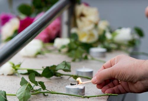 Es werden Kerzen angezündet und Blumen niedergelegt. (Bild: AP/Sebastian Widmann)
