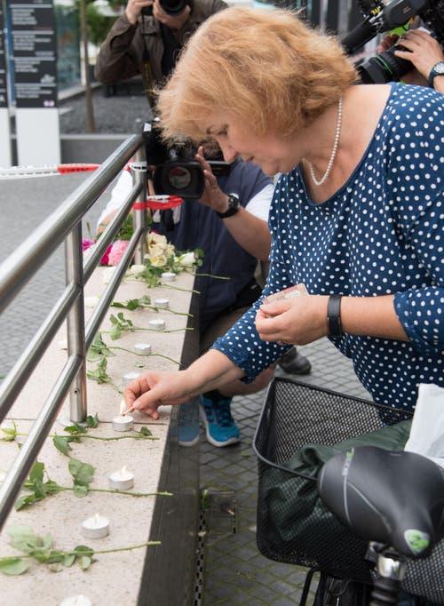 Eine Frau zündet eine kerze an. (Bild: AP/Sebastian Widmann)