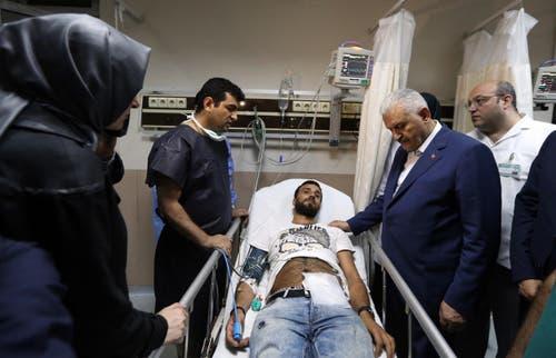 Der türkische Ministerpräsident Binali Yildirim, zweiter von rechts, besucht einen verletzten Mann nach dem Anschlag im Krankenhaus. (Bild: Hakan Goktepe)