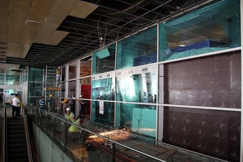 Bauarbeiter ersetzten die kaputten Wände des Flughafens. (Bild: AP Photo/Bram Janssen)