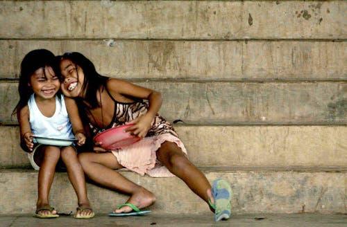 Zwei Mädchen lachen während des Essens in einem Evakuierungscamp auf den Philippinen am 26. Mai 2003. (Bild: Keystone)