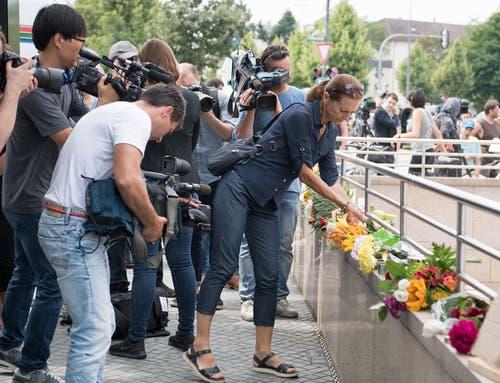 Trauern in der Öffentlichkeit: Eine Frau legt Blumen nieder. Zahlreiche Journalisten halten diesen Moment mit ihren Kameras fest. (Bild: Keystone / Sebastian Widmann)