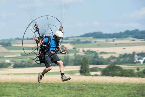 """Ein Mann demonstriert sein Trike unter dem Motto """"Piste frei für elektrische Ultraleichtflugzeuge"""" auf dem Flugplatz in Schaffhausen. (Bild: Keystone / ENNIO LEANZA)"""