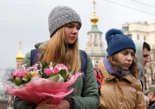 Zwei Frauen mit Blumen vor der französischen Botschaft in Moskau. (Bild: EPA/Sergei Chrikov)