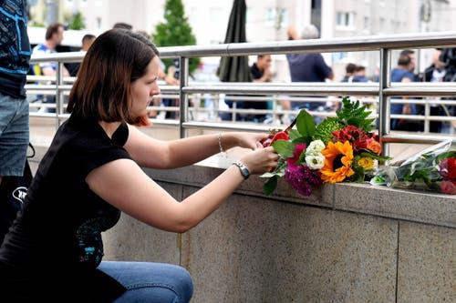 Eine Frau legt Blumen nieder. (Bild: Kerstin Joensson)