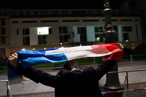 Ein Mann hält die «Tricolore» hoch. (Bild: AP/Gregor Fisher)