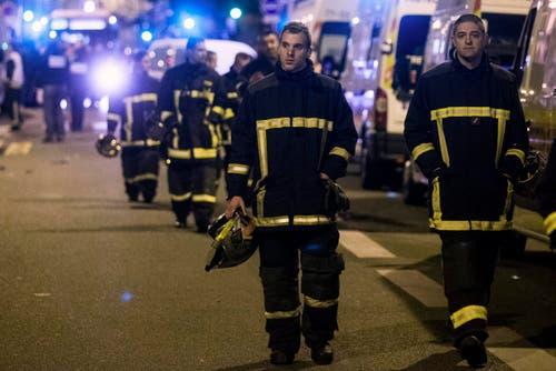 Die Fassungslosigkeit steht diesen Rettungskräften ins Gesicht geschrieben. (Bild: EPA/Etienne Laurent)