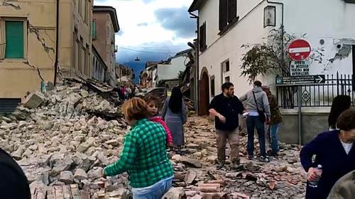 Überlebende in den Trümmern von Amatrice. (Bild: AP Photo / Videostill)