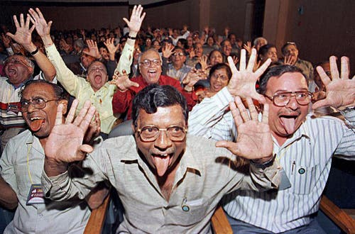 Mitglieder eines Lachclubs schneiden Grimassen während einer Lachveranstaltung in Bangalore, am 23. Dezember 2001. Die meisten der 900 Teilnehmer sind überzeugt, dass Lachen gut für ihre Gesundheit ist. (Bild: Keystone)