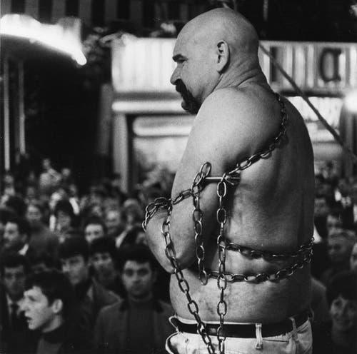 Kettensprenger Charly de Kiswarth demonstriert an der Luzerner Herbstmesse seine Kraft, 1960 (Bild: Foto: Ernst Scagnet/Stadtarchiv Luzern)