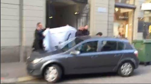 Für die Öffentlichkeit begann die Justiz-Aktion so: Eine Person mit Geleitschutz wird in einen wartenden Wagen geführt. Das Bild stammt von einem Handyvideo vom Mittwoch und wurde am Seiteneingang des Hotels Baur au Lac aufgenommen. (Bild: AP Photo / Rob Harris)