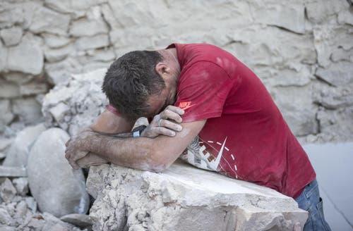 Ein Mann beugt sich über einen Trümmerstein in Amatrice. (Bild: AP / Massimo Percossi)
