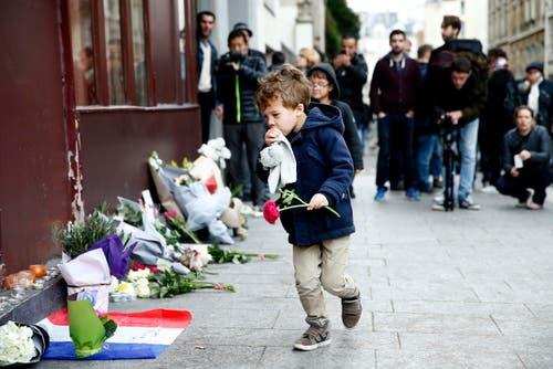 Ein kleiner Knabe legt vor dem Cafe Carillon in Paris Blumen nieder. (Bild: EPA/Yoan Valat)