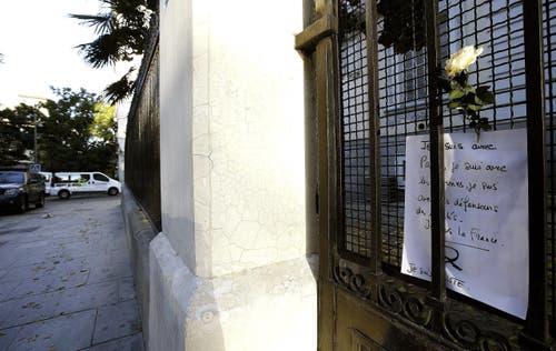 Eine weisse Rose und eine handgeschriebene Notiz vor der französischen Botschaft in Madrid. (Bild: EPA/Angel Diaz)