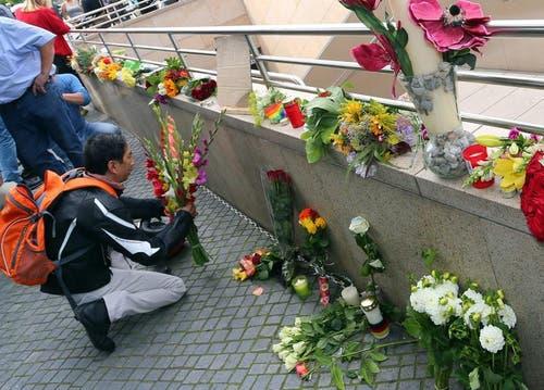 Ein Mann verleiht seiner Trauer Ausdruck und legt Blumen nieder. (Bild: Keystone)