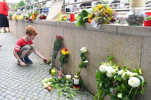 Der Junge bringt wie viele andere Menschen Blumen und Kerzen für die Opfer des Amoklaufes zum Einkaufszentrum. Am Freitagabend erschoss ein 18-Jähriger dort 9 Menschen. (Bild: Keystone)