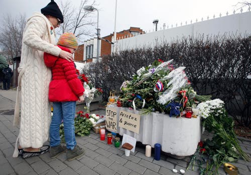 Eine Frau und ein Kind stehen vor den Blumen bei der französischen Botschaft in Moskau. (Bild: EPA/Sergei Chrikov)