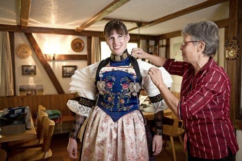 Vreni Kaiser, rechts, hilft Silvia Gut die Tracht anzuziehen. (Bild: Corinne Glanzmann / Neue NZ)
