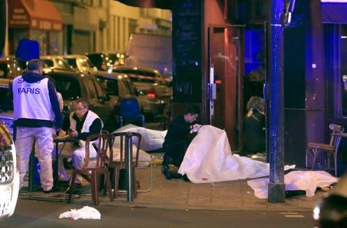 Polizisten bei der Spurensicherung, Opfer des Anschlags sind mit Tüchern bedeckt. (Bild: AP/Thibault Camus)