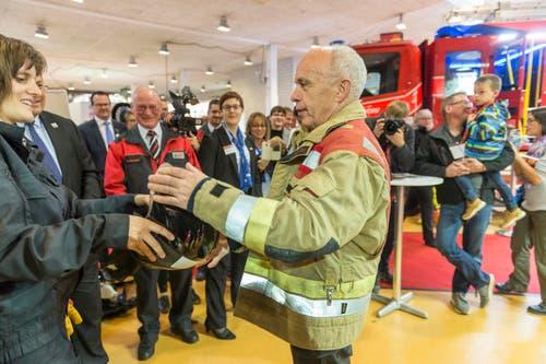 Über den Anzug die Feuerwehrausrüstung: Maurer lässt sich einen Helm reichen. (Bild: Hanspeter Schiess)