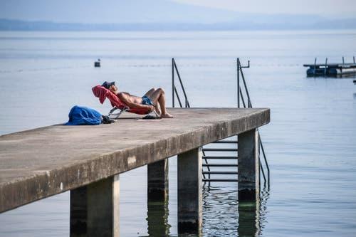 Im Strandbad Uttwil gönnt sich ein Mann ein Sonnenbad. (Bild: Ralph Ribi)