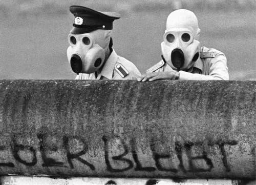 Mit Gasmasken ausgerüstet blicken DDR-Grenzsoldaten am 21. Juni 1988 über die Mauer am Potsdamer Platz in Berlin. (Bild: Keystone)