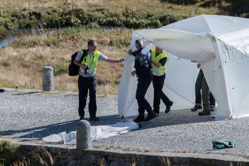 Am Boden liegt die abgedeckte Leiche eines Piloten. (Bild: Keystone)