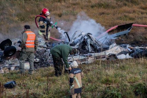 Feuerwehrleute löschen die brennenden Trümmer des Helikopters. (Bild: Keystone)