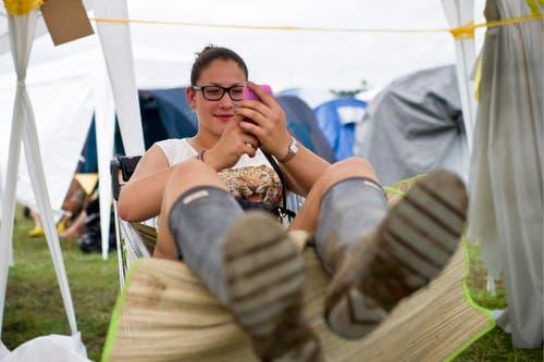 Gummistiefel für den Schlamm, kurze Hosen für die Sonne - und das Handy für die Freunde. (Bild: Keystone)